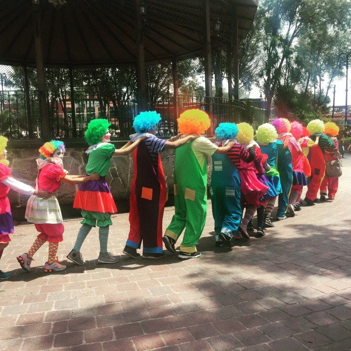 Sunday afternoon in the park and a conga line of clowns go by